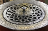 Foot warmer, Bidri: Bidri work is black in colour, never fades or rusts, and is inlaid with silver. The alloy used in making Bidri comprises tin and copper in a proportion of 24:1. It was introduced into India [Bidar, Karnataka] from Persia in the 14th Century.