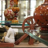 Lac is the resinous incrustation formed on the bark of trees by lac insects. In lac-ware battis, or sticks of lac, are applied onto wooden articles for decoration. The model demonstrates the multi-faceted and laborious process involved in making this art product.