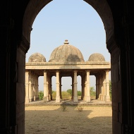 Kevada Masjid's cenotaph, with its four cupolas surrounding a bigger central dome, seen through an archway of the mosque.