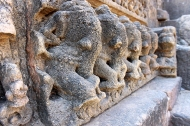 Rows of life-like prancing elephants line the outer base of the platform or pitha on which the temple stands.