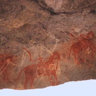 Painters in Bhimbetka oftentimes painted over existing paintings, creating upto 15 layers of superimpositions. The dark ochre compositions belong to the beginning of the Mesolithic period. The compositions in lime are newer in comparison.