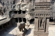 Kailasha stambha and a carved stone elephant inside the courtyard: The stambha or obelisk is 17 metres high and inscribed with the words: Elura. Dhvaja Stambha. Kailasa.