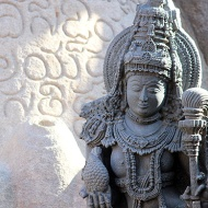 An ornately carved Hoysala period Yakshi guards the hero-deity.